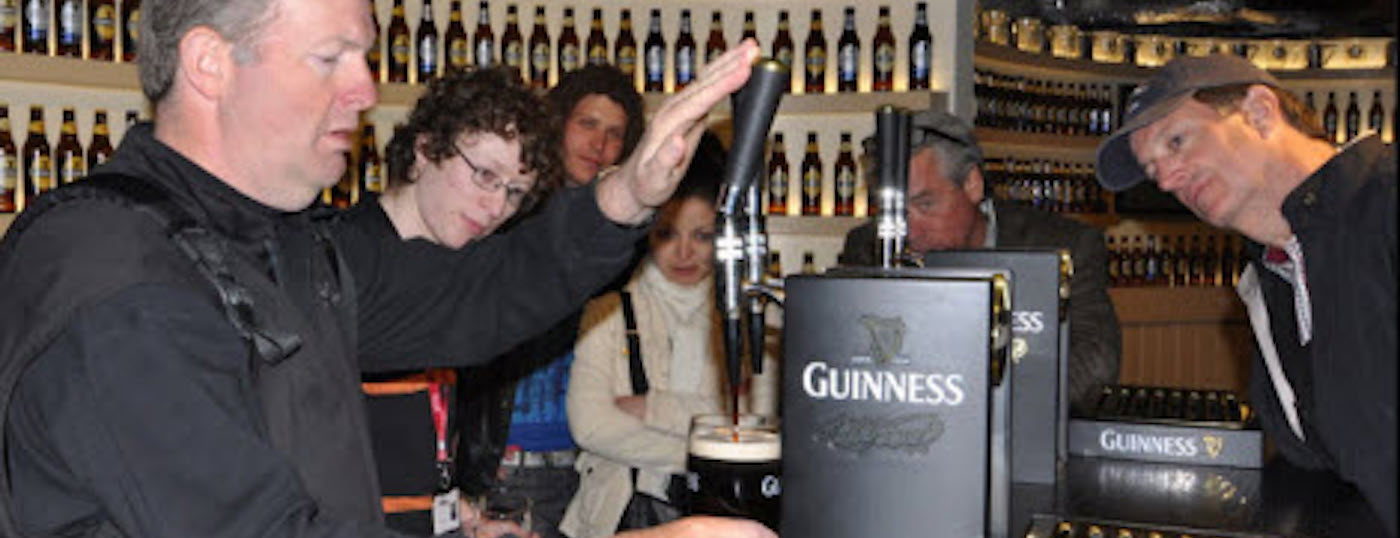 Executive Tours Ireland Holidaymakers watching the art of Guinness being poured